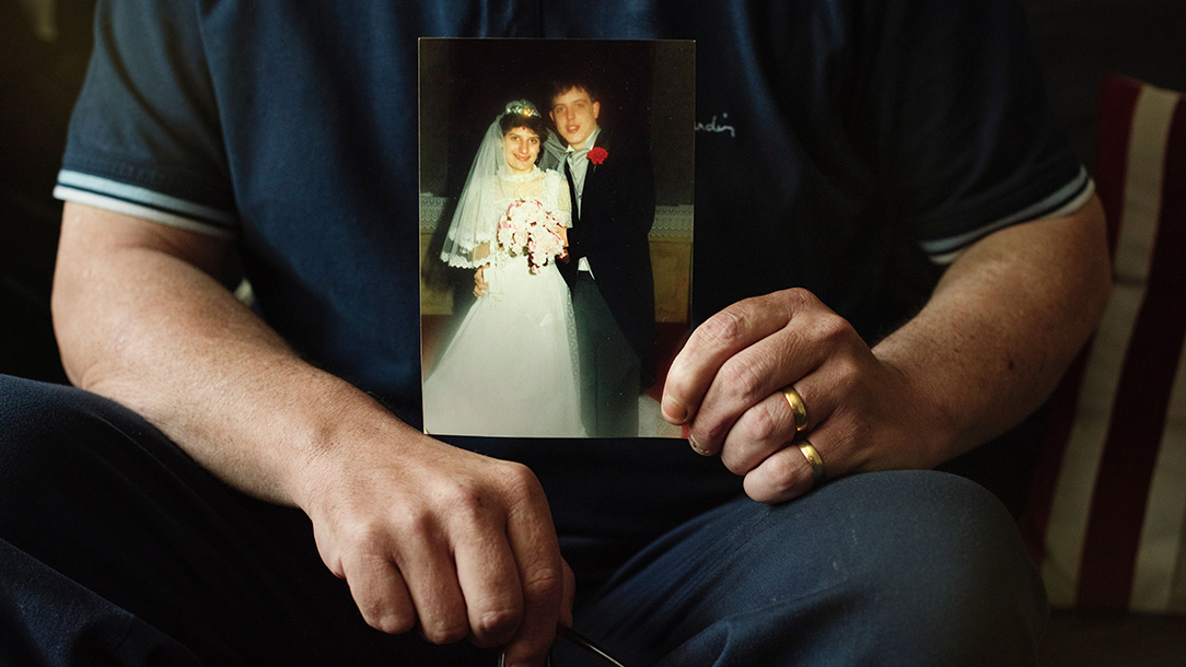 Wayne O'Hanlon holding a photograph of himself and his wife on their wedding day.
