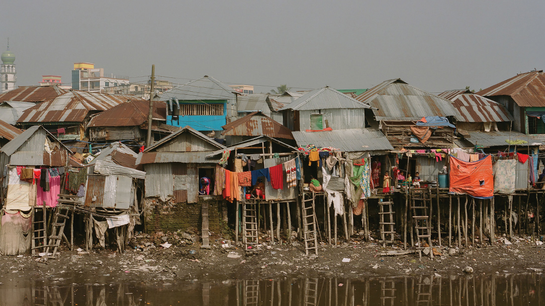 Houses built on thin poles to hold them up in case of floods line a river bank in Barishal, Bangladesh.