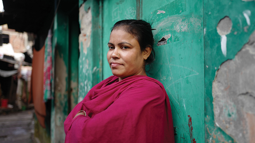 In Bangladesh, Josna stands against a wall smiling with her arms folded,