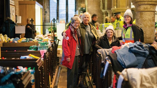 British Red Cross volunteers and people whose homes have been flooded stand together in a church surrounded by donated clothes and food.