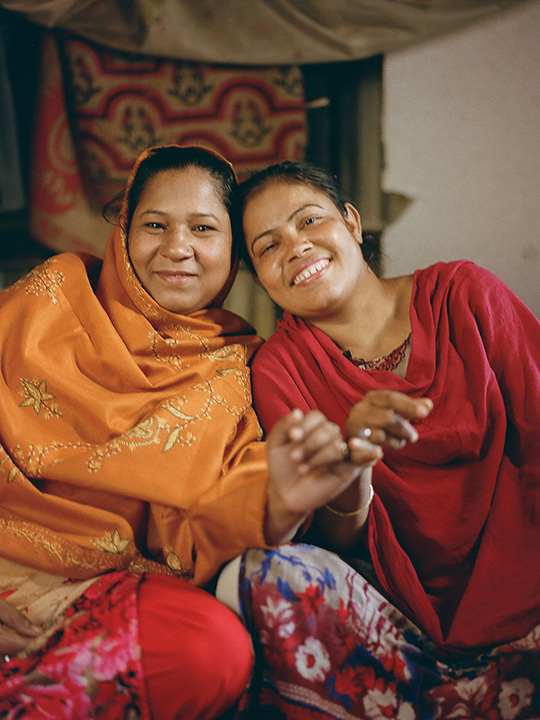 Josna and her friend Mahmouda in Barishal, Bangladehs, smile and lean against each other