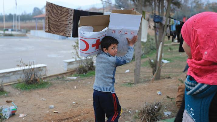In Syria, a boy carries a very large food parcel from the Red Cross and Red Crescent.