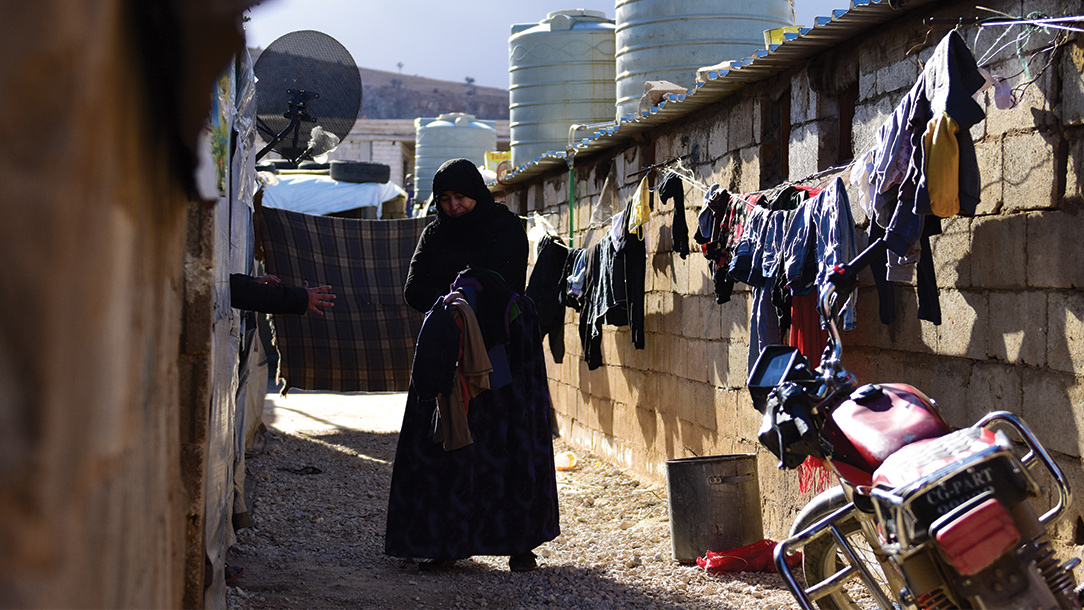 A Syrian refugee in Lebanon walks in a narrow alley between two houses where laundry is hanging to dry.