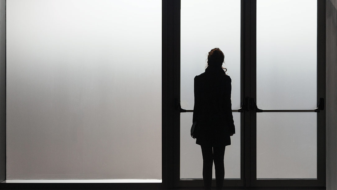 A young woman standing looking out very large windows.