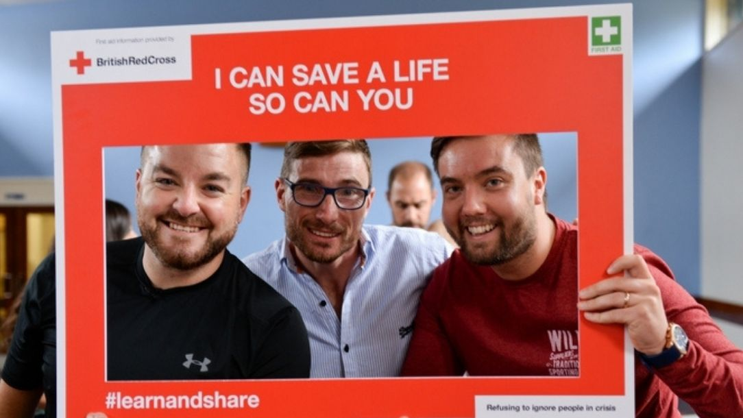 "Presenter Alex Brooker and two of his friends attend a British Red Cross first aid course and hold up a sign saying ""I can save a life, so can you""."