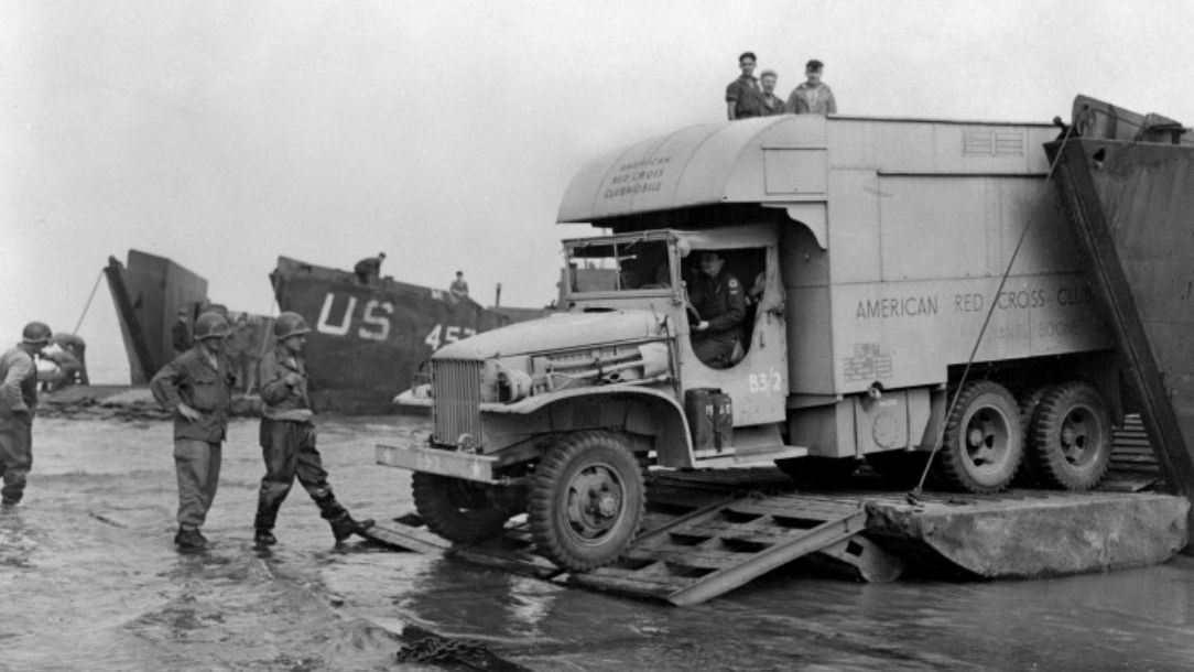 A black and white photograph showing a large Red Cross truck arriving in Normandy, with soldiers looking on.