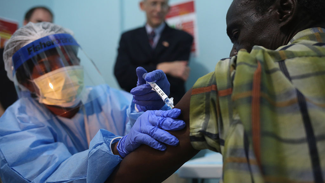 A health worker vaccinates a man against Ebola.