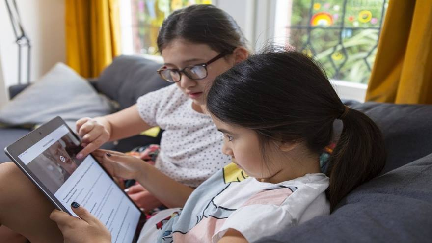 Two sisters learning first aid at home on a tablet