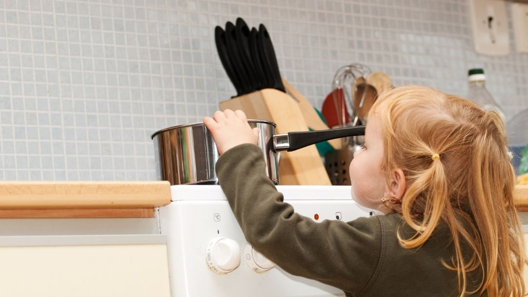 A little girl about to pull a hot saucepan off the stove and is in danger of burning herself.