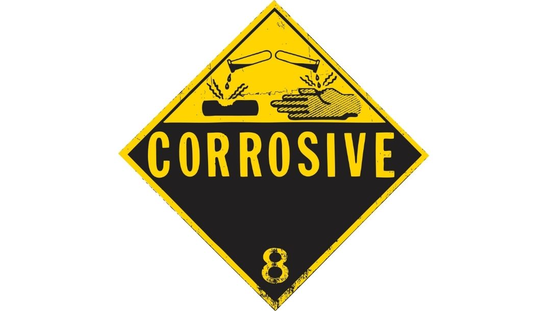 A yellow and black acid burn warning sign, showing illustrations of corrosive liquid and a damaged hand, with the world 'corrosive' in big letters.