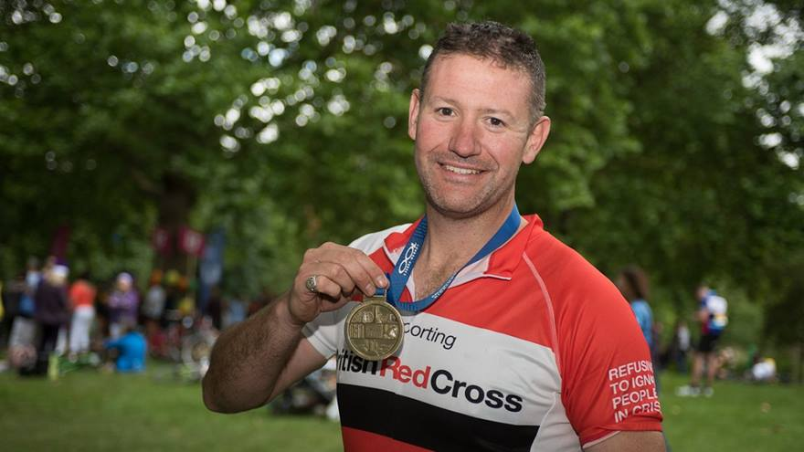 Man holding up his medal after completing the event.