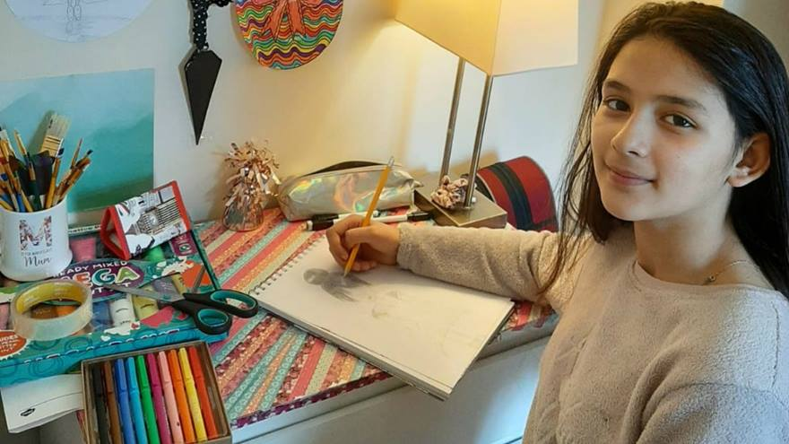 A girl sits at a table drawing with coloured pencils and looking at the camera.