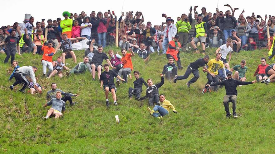 A crowd watching people take part in a cheese rolling competition.