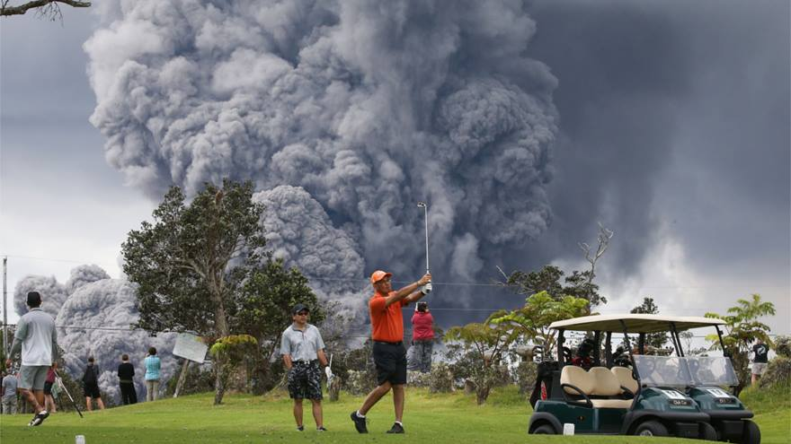 Person playing golf in front of an ash cloud in Hawaii