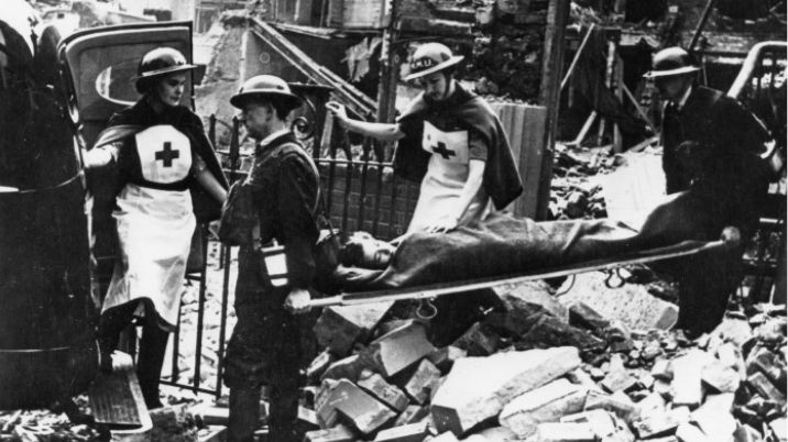 A black and white photograph showing British Red Cross workers helping civilians after an air raid in 1940-1945