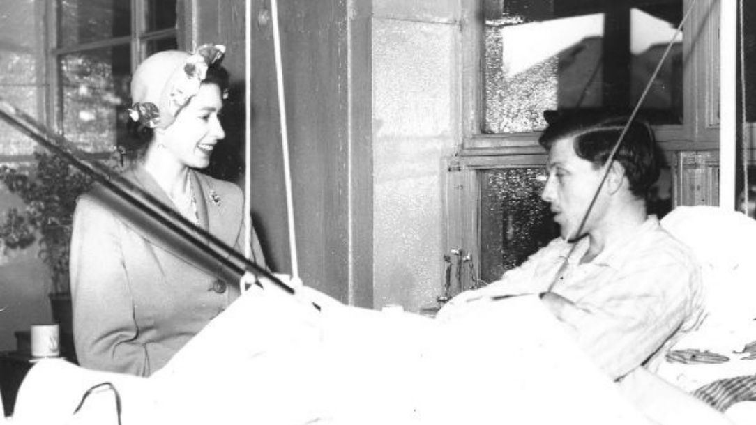 A black and white photograph of smiling Queen Elizabeth II visiting an injured male service user.