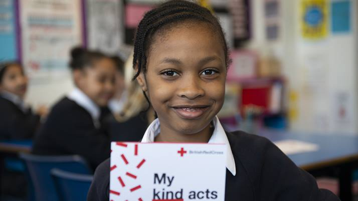 Image of little girl holding a British Red Cross branded folder entitled 'My kind acts', and smiling.