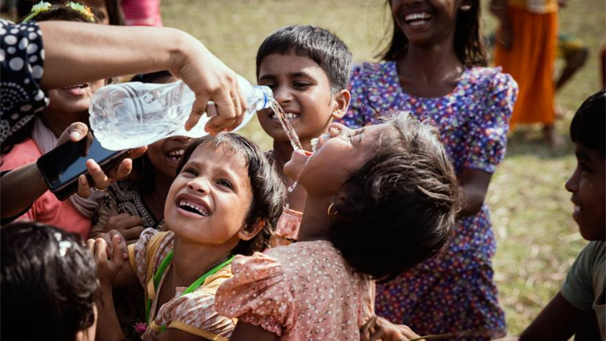 Rohingya children smile as they drink and play with water.