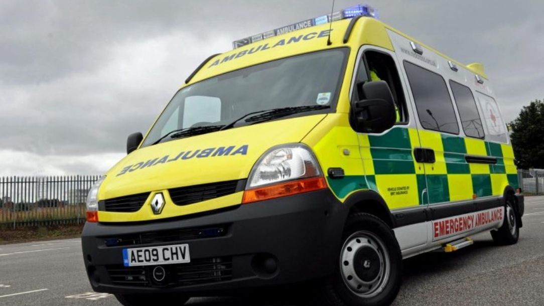 A yellow and green NHS ambulance driving at speed.