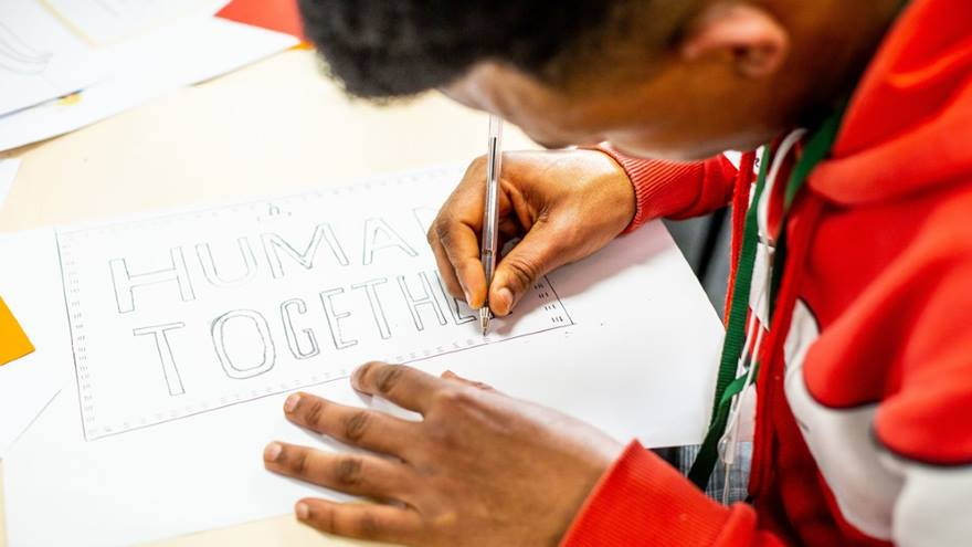 Young person taking part in a refugee art project. Drawing 'human together'