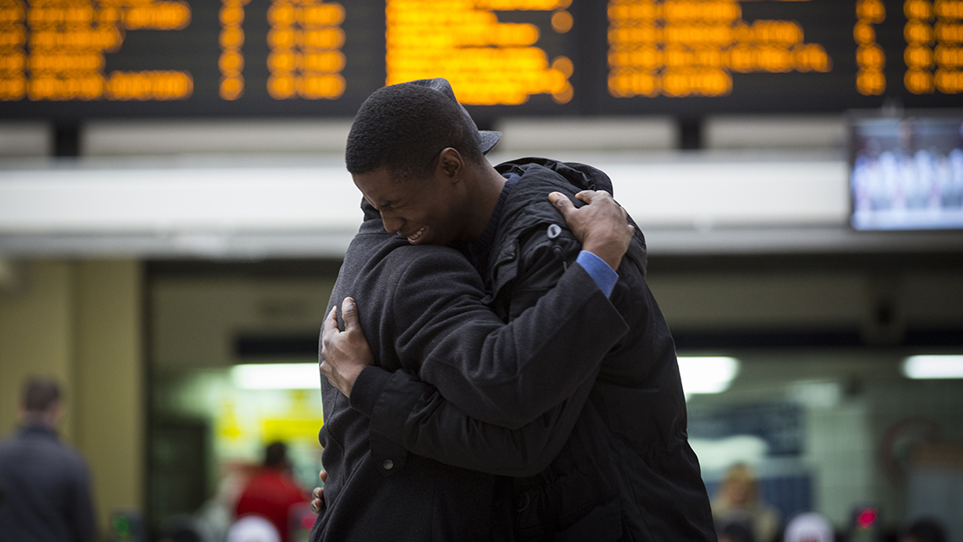 A father and son embrace after being reunited at London Kings Cross station