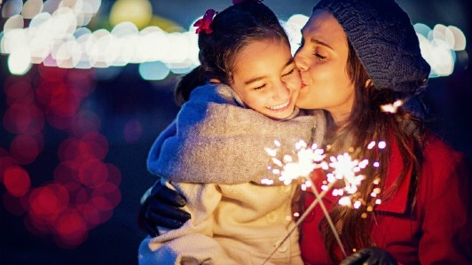 A mother hugs and kisses her daughter as they both hold sparklers.