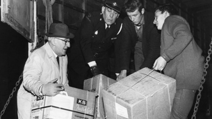 Two police officers and two other men lift cardboard boxes into the back of a van at the time of the mining disaster in Aberfan.