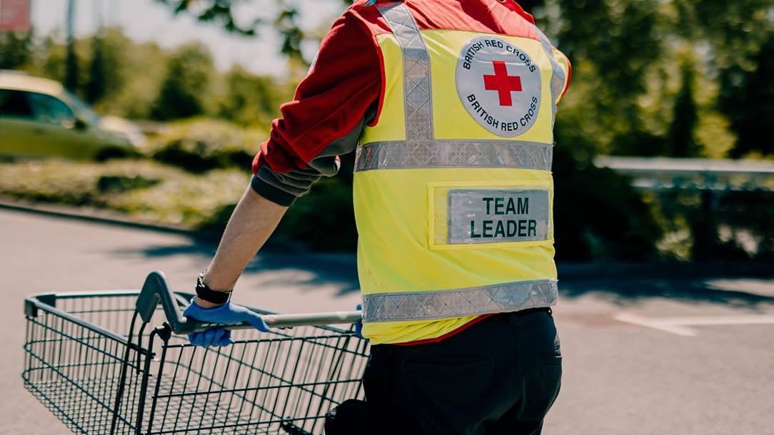 John, a doctor and Red Cross emergency volunteer team leader, wears a vest that says Team leader and pushes a shopping card as he walks away from the viewer.