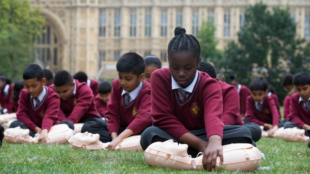 Children from Ark Oval Primary Academy School in South London practise first aid on dummies on the lawn in front of the UK Houses of Parliament.