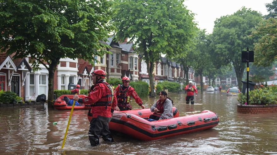 A woman is rescued in a flooded street.
