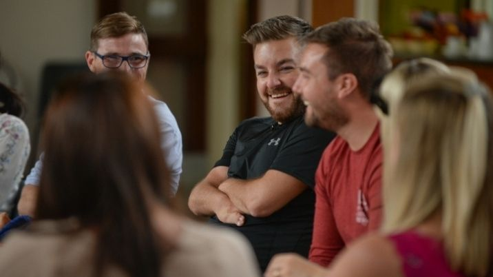 Presenter Alex Brooker laughs with friends at a British Red Cross first aid course