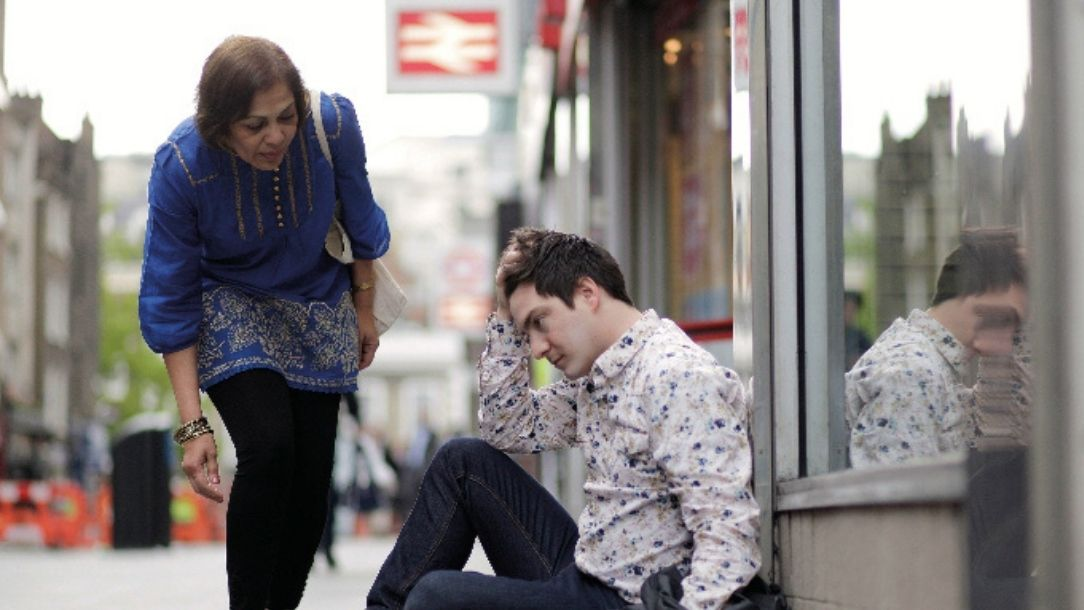 A concerned woman approaches a man sitting on the ground outside a train station.