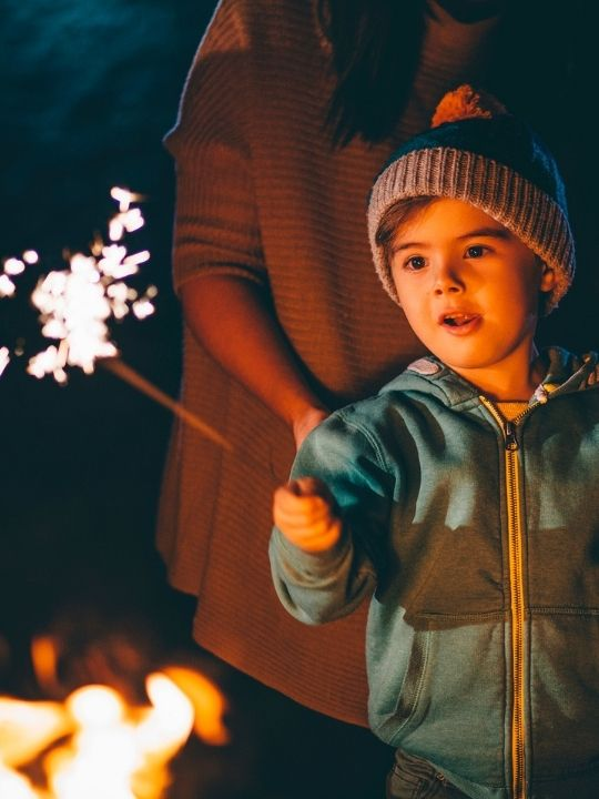 Little boy waving a sparkler on bonfire night