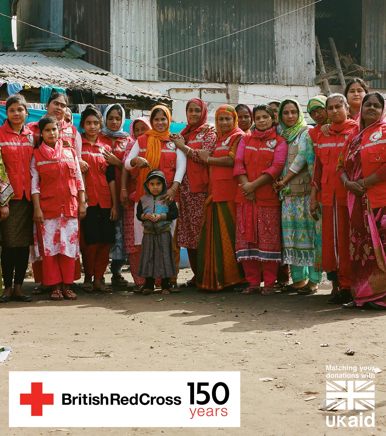In Bangladesh, a group of women getting support to start small businesses from the Red Cross and Red Crescent stand in a line with their arms on each other's shoulders.
