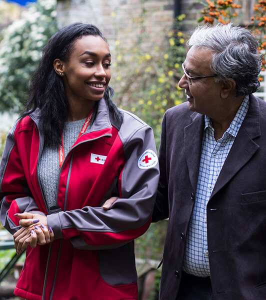 British Red Cross volunteer helps an older man get out and about
