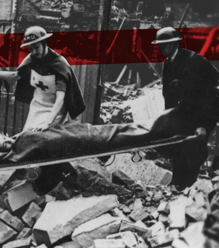 During the Blitz in the Second World War, British Red Cross volunteers carry someone on a stretcher over the rubble of buildings that have been bombed.