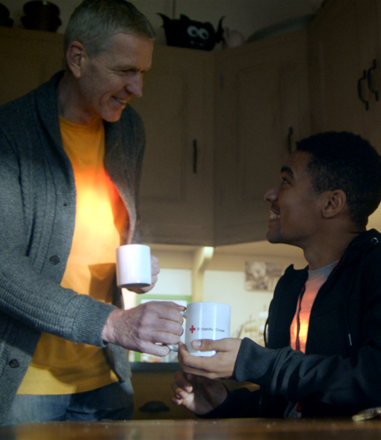 A man offers another man a cup of tea - a scene from the British Red Cross brand campaign film