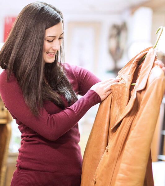 Young Woman Admires Jacket On A Hanger in a charity shop