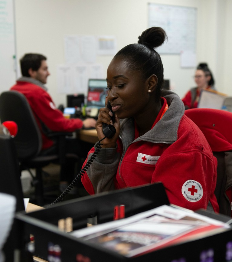 A British Red Cross volunteer speaks on the phone while other volunteers sit at desks behind her.
