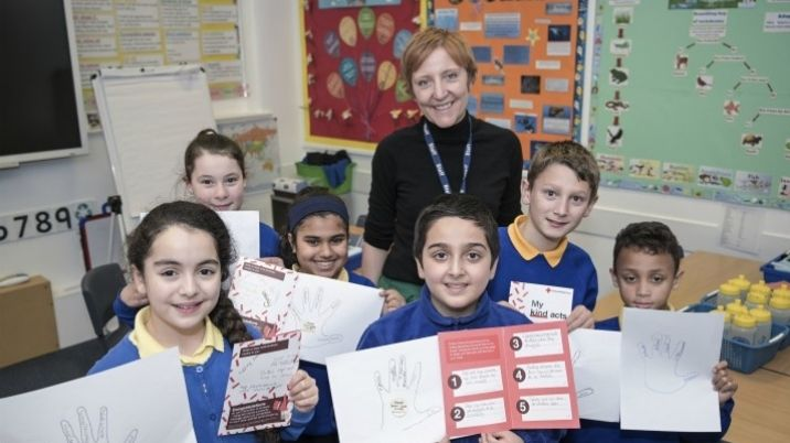A teacher and her class show off their British Red Cross Power of Kindness workbooks
